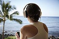 USA, Hawaii, woman with headphones and smartphone in front of the sea, back view - STKF001094