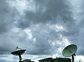 USA, Hawaii, Ka Lae, satellite dishes in front of cloudy sky - STKF001103