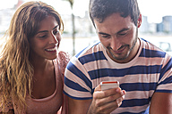 Young couple sending messages with a smartphone - MGOF000003