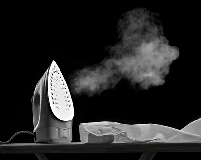 Steaming flat iron and shirt sleeve in front of black background - RAMF000002