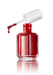 Bottle of red nail polish in front of white background - RAMF000016