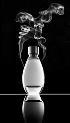 Smoking perfume bottle in front of black background - RAMF000022