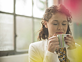 Young businesswoman enjoying cup of coffee - UUF002910