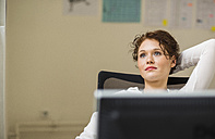 Young woman in office thinking - UUF002919