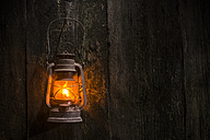 Lighted old gas lantern hanging on wooden wall - DEGF000070
