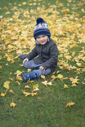 Smiling toddler sitting on a meadow covered with autumn leaves - MW000082