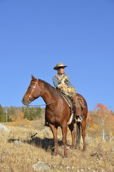 USA, Wyoming, Big Horn Mountains, riding cowgirl in autumn - RUEF001316