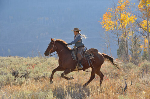 USA, Wyoming, Big Horn Mountains, riding cowgirl in autumn - RUEF001317