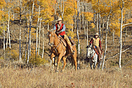 USA, Wyoming, Big Horn Mountains, riding cowgirl and cowboy in autumn - RUEF001325