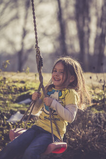 Smiling little girl sitting on a swing - SAR001166