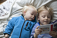 Two little boys lying on blanket watching book - RB002187