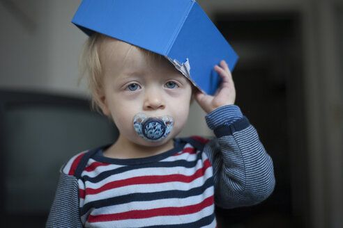 Portrait of little boy with pacifier and blue cardboard box on his head - RB002202