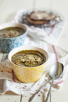 Bowls of Saag spiced with chili flakes on cloth - SBDF001536
