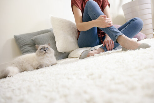 Longhair cat and woman relaxing on a carpet at home - NNF000064