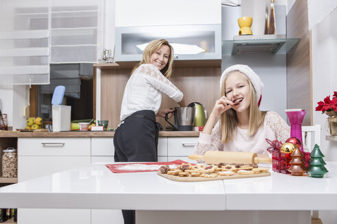 Mother and daughter baking Christmas cookies at home - VTF000373