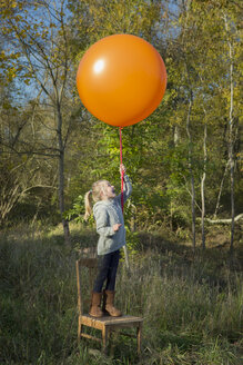 Girl standing on chair holding balloon on meadow - JTLF000016