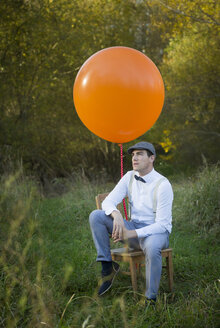 Man sitting on chair with balloon on meadow - JTLF000018