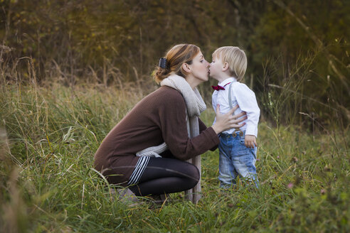 Mother kissing son on meadow - JTLF000011