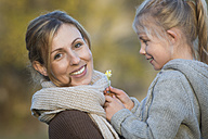 Happy mother and daughter with daisy outdoors - JTLF000003