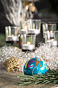Christmas decoration, Blue christmas bauble and candles in the background - JUNF000136