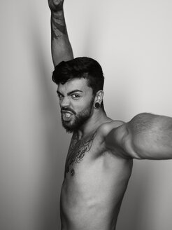Portrait of angry shirtless man with outstretched arms - STK001122