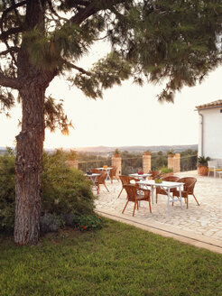 Spain, Majorca, terrace in a small hotel complex, tree, sunset - MS004396