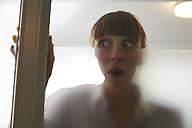 Frightened woman behind glass pane - STKF001136