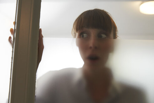 Frightened woman behind glass pane - STKF001136