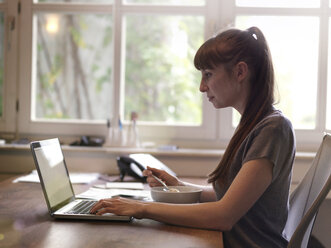 Woman at desk using laptop and eating muesli - STKF001157