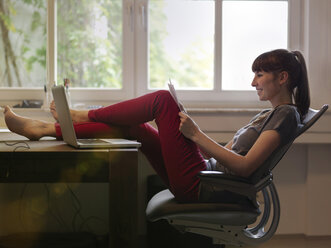 Woman with feet on desk reading paper - STKF001190
