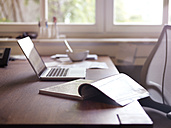 Magazine and laptop on desk - STKF001168