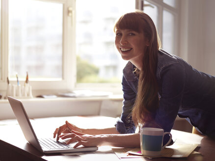 Portrait of smiling woman at desk using laptop - STKF001180