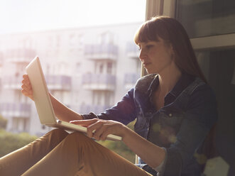 Woman at open window using laptop - STKF001181