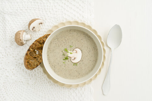 Creme of mushroom soup in white soup bowl, baguette slice - ECF001636