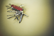 Swiss army knife on green background - MF001343