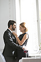 Elegant couple embracing in restaurant - WESTF020389