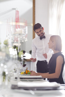 Waiter serving dinner to woman in elegant restaurant - WESTF020416