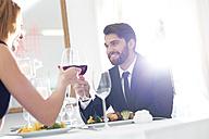 Elegant couple toasting wine glasses in restaurant - WESTF020425