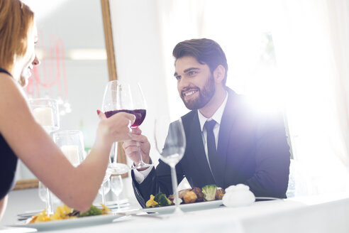 Elegant couple toasting wine glasses in restaurant - WESTF020425