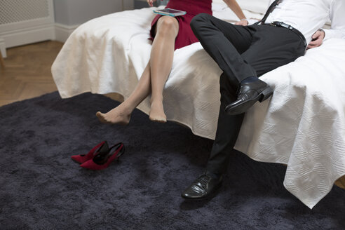 Elegant couple using digital tablet in bed - WESTF020446