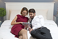 Elegant couple using digital tablet in bed - WESTF020449
