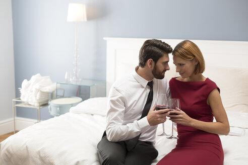 Affectionate couple holding wine glasses in bedroom - WESTF020455