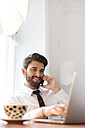 Businessman with laptop and cup of coffee on cell phone - WESTF020479