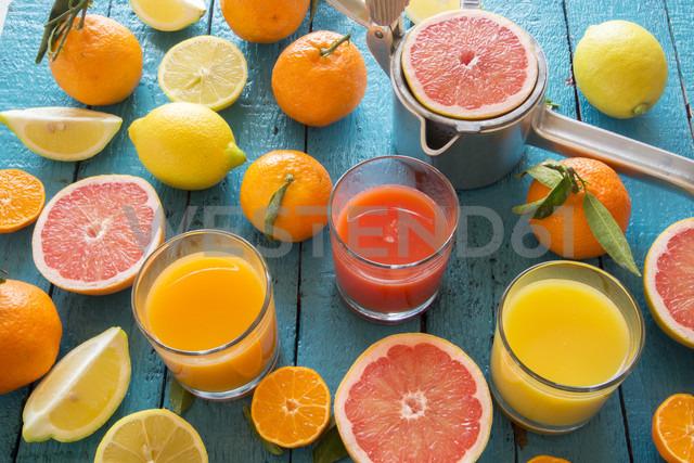 Glasses of orange juice, grapefruit juice and multivitamine juice, juice squeezer and fruits on wood - SARF001197
