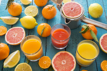 Glasses of orange juice, grapefruit juice and multivitamine juice, juice squeezer and fruits on wood - SARF001197