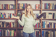 Woman with book and tablet pc in front of bookshelf, smiling - SAR001209