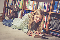 Woman reading a book, bookshelf in the background - SAR001211
