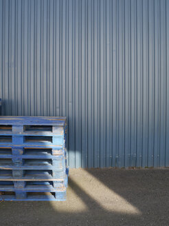 Stack of blue wooden pallets in front of blue steel sheet facade - JMF000306