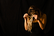 Woman disentangling her hair in front of black background - TCF004472