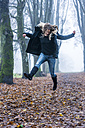Woman jumping into the air on a forest track - TCF004496